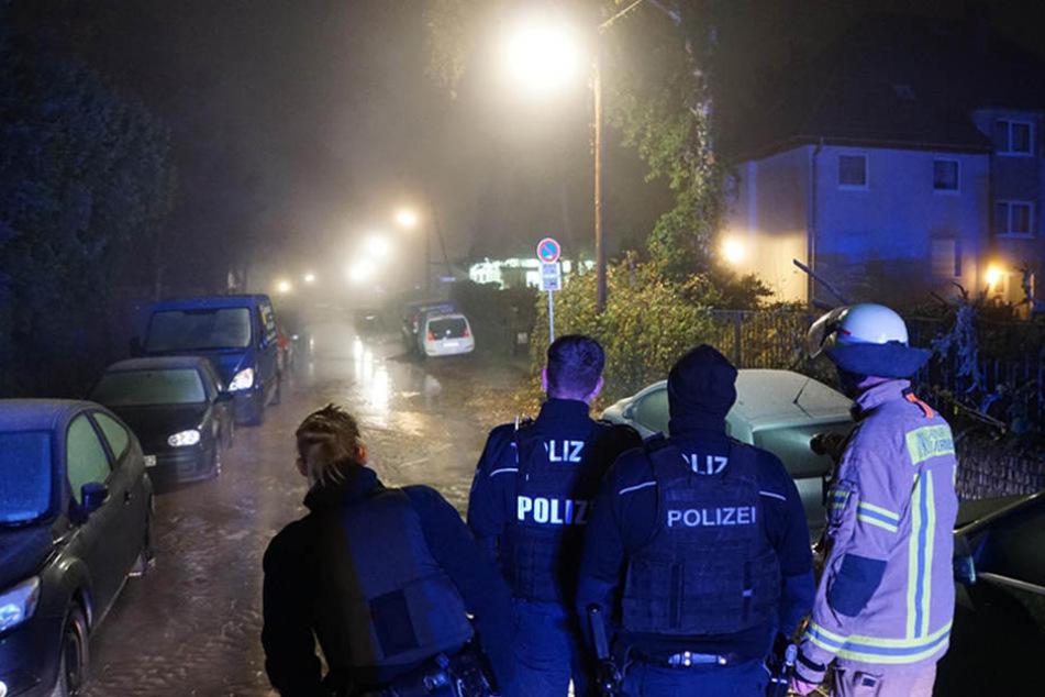 Polizei und Feuerwehr blicken auf den gefluteten Ostburger Weg.