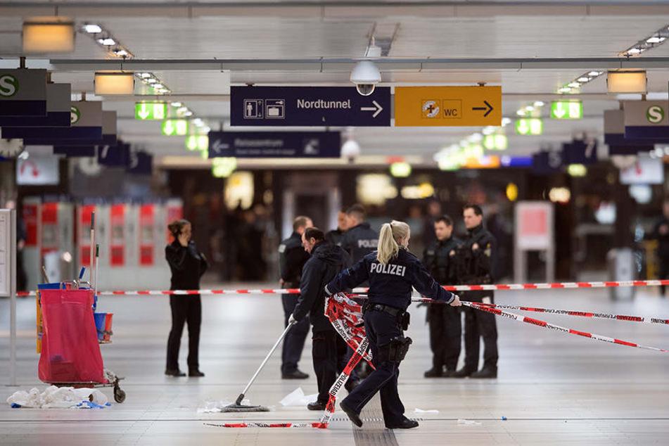 Polizisten entfernen im Hauptbahnhof von Düsseldorf die Absperrbänder.
