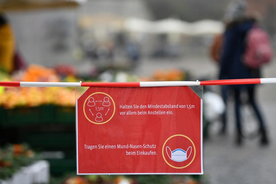 In Erfurt sind Verhaltensregeln für den Wochenmarkt auf einem Schild am Domplatz zu sehen.