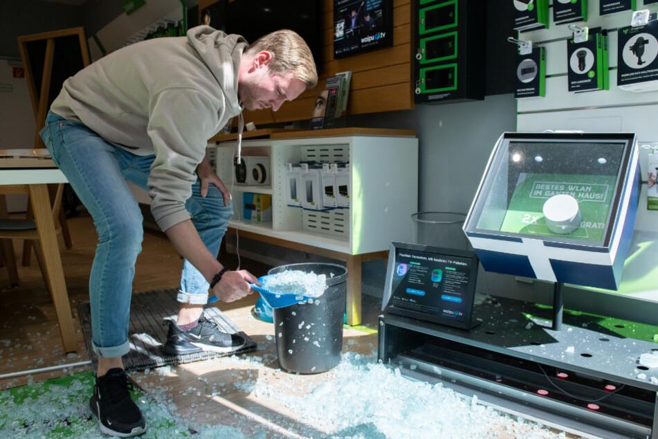 Ein Mitarbeiter eines Handyladens räumt Scherben auf.