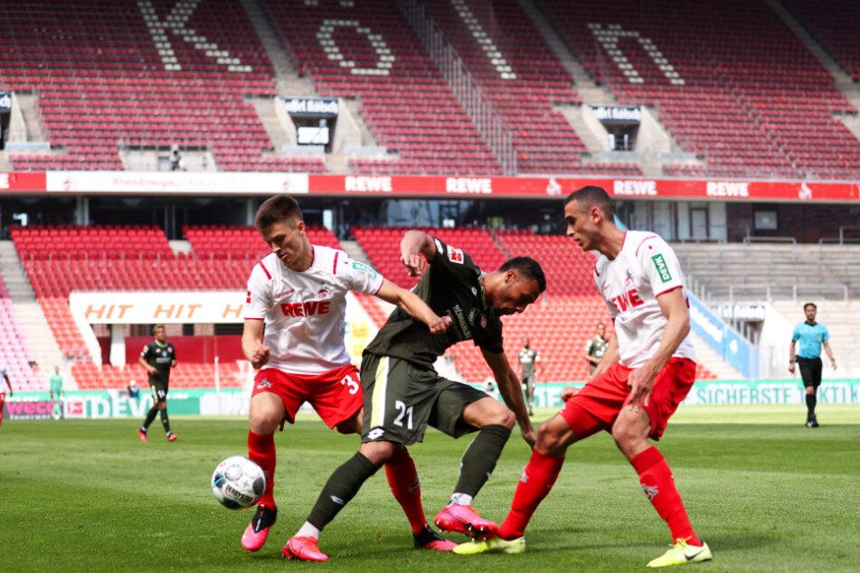 Noah Katterbach (l.) und Ellyes Skhiri (r.) luchsen dem auffälligen Mainzer Karim Onisiwo mit vereinten Kräften und vor gähnend leeren Rängen den Ball ab.