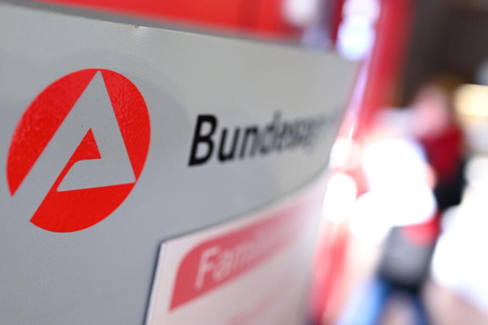 """Ravensburg: Auf einer Stele ist das Logo der """"Bundesagentur für Arbeit"""" zu sehen, während im Hintergrund ein Besucher am Informationsschalter steht. (Symbolbild)"""