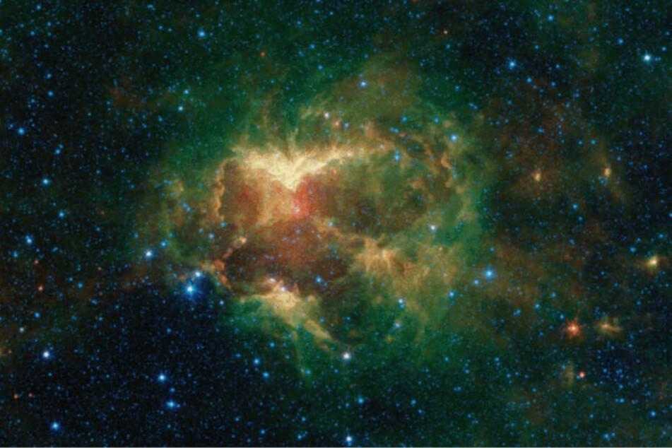 Ein massereicher Stern erschafft in der Mitte einer Staub- und Gaswolke einen weitläufigen Nebel. Optisch erinnert dies an das Gesicht eines Ghuls.