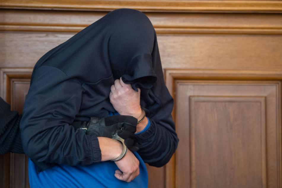 Der Angeklagte im Prozess um einen Dreifach-Mord wird im Landgericht im Gerichtssaal von Justizbeamten an seinen Platz geführt. (Archivbild)
