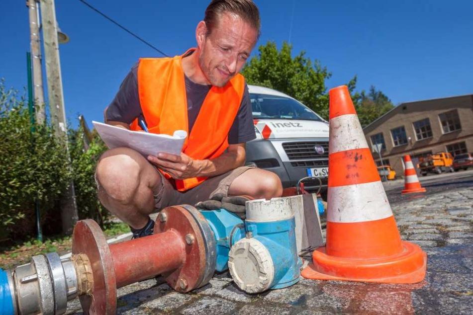 """Konzentriert zwischen Wasser und Sonne - """"iNetz""""-Mitarbeiter Ronny koch (40) überprüft die Wassermengen in Kleinolbersdorf."""