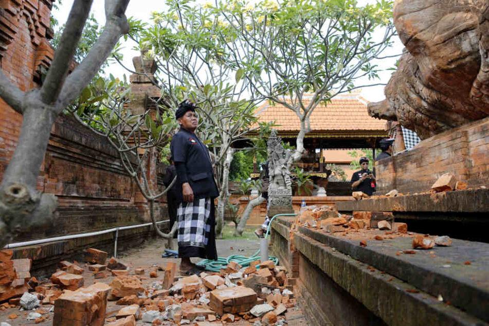 Ein Mann steht neben einem beschädigten Tempel.