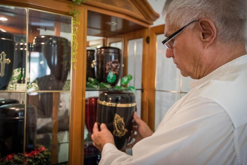 Bestatter Olaf Schuster (55) zeigt eine Auswahl an Urnen.