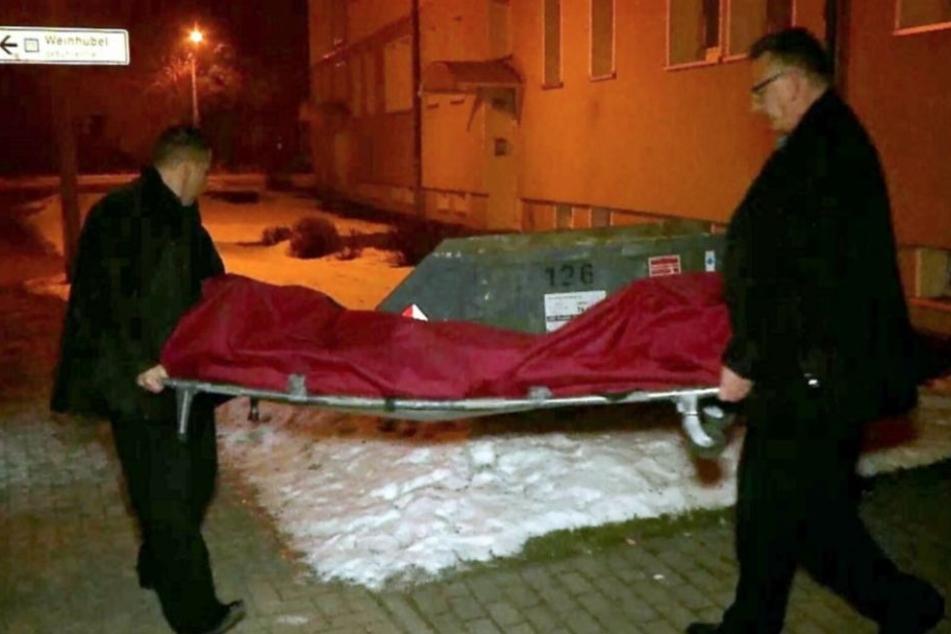 Die Leiche des Toten wird aus der Wohnung getragen.