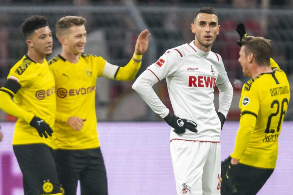 Kölns Ellyes Skhiri ist enttäuscht, während im Hintergrund v.li. Dortmunds Jadon Sancho, Dortmunds Marco Reus und Dortmunds Lukasz Piszczek das Tor zum 2:0 feiern.