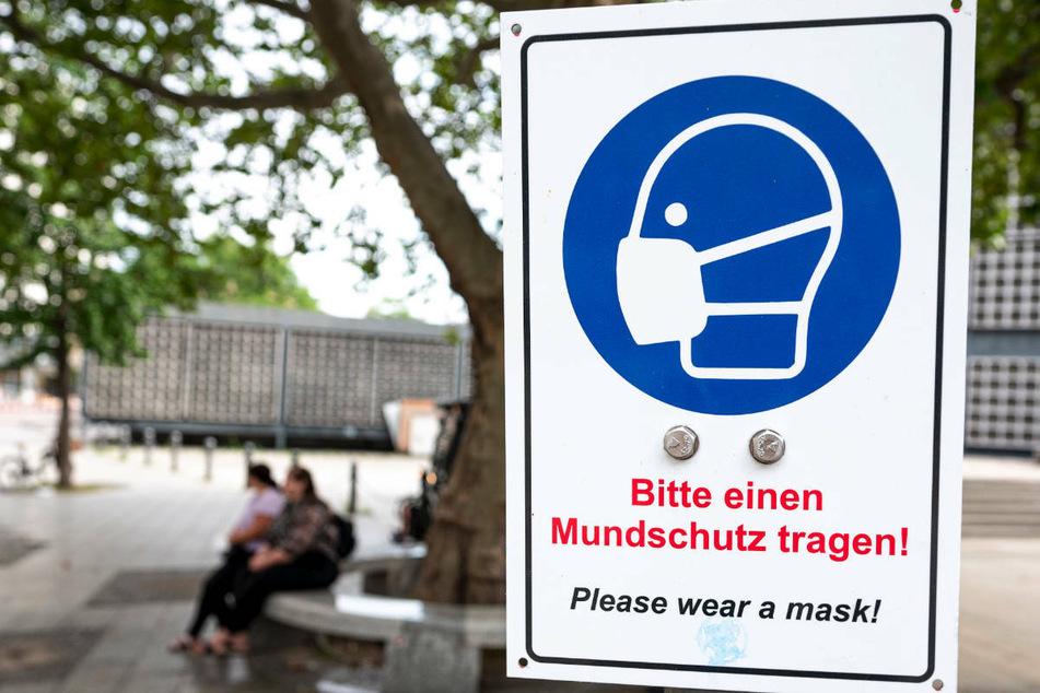 Ein Schild mit der Aufschrift «Bitte einen Mundschutz tragen!» hängt am Kurfürstendamm. Die Corona-Zahlen in Berlin steigen.