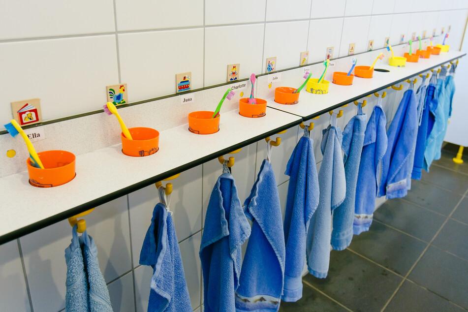 Zahnbürsten in Zahnputzbechern stehen auf einem Regal über Handtüchern auf der Toilette einer Kindertagesstätte.