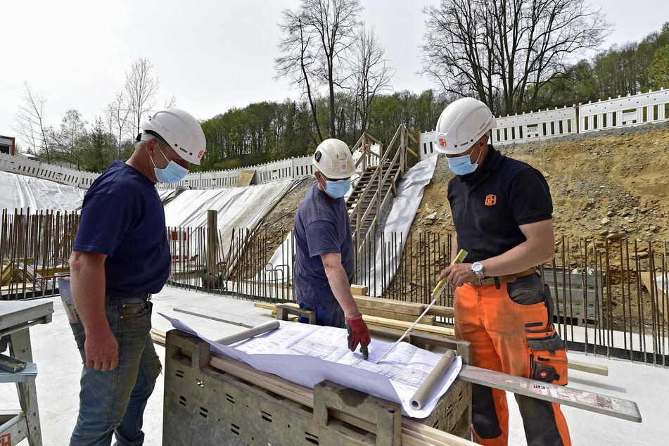 Bauberatung nur noch im Freien: Ronny Schönherr (43), André Haase (44) und Betonbaupolier Dennis Paschke (43) besprechen sich.