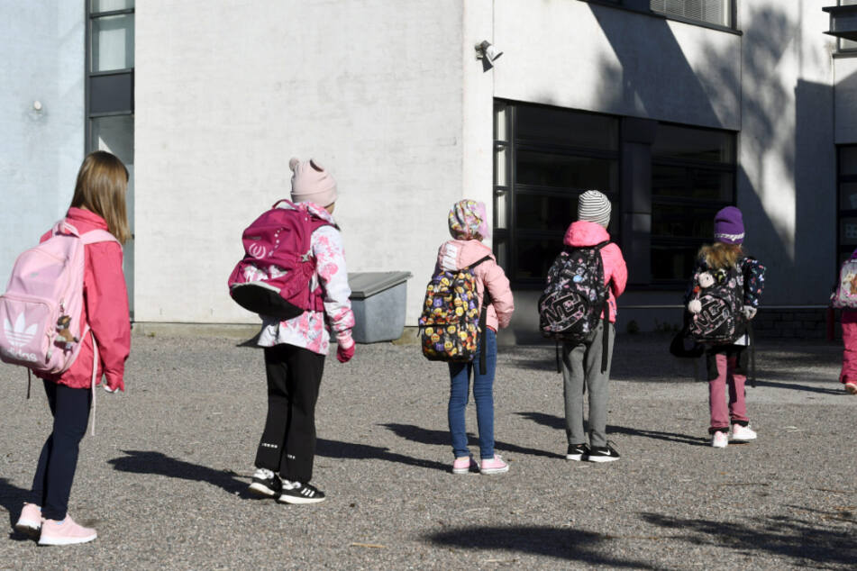 Schüler stehen unter Einhaltung eines Mindestabstands vor einer Grundschule an.