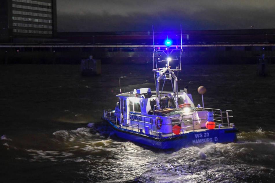 Ein Polizeiboot sucht mit Scheinwerferlicht die Elbe nach dem Vermissten ab.