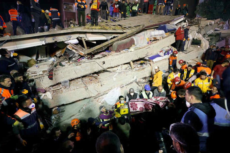 Hier bergen die Retter einen Überlebende aus den Trümmern des eingestürzten Hauses.