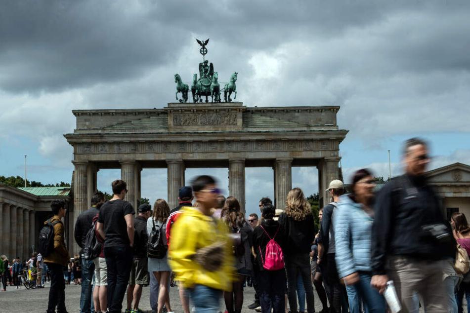 Dunkle Wolken ziehen über das Brandenburger Tor, während zahlreiche Menschen auf dem Pariser Platz stehen.