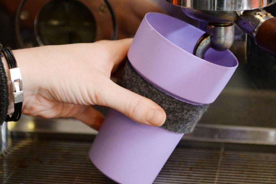 Ein Kaffeebecher wird in einem Cafe mit Kaffee gefüllt. Er ist eine umweltfreundliche Variante.