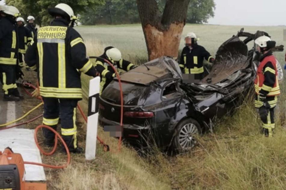 Sichtlich mitgenommen stehen die Feuerwehrmänner neben dem völlig zerstörten Alfa Romeo. Der Fahrerin konnten sie nicht mehr helfen.