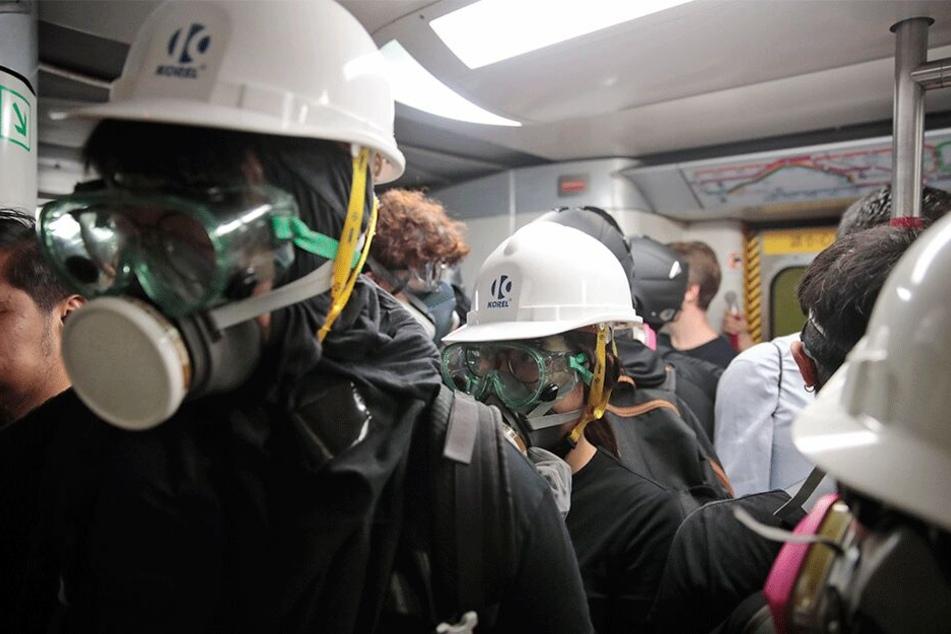 Mit Gasmasken und Helmen ausgestattete Demonstranten fahren im Zug nach Causeway Bay.