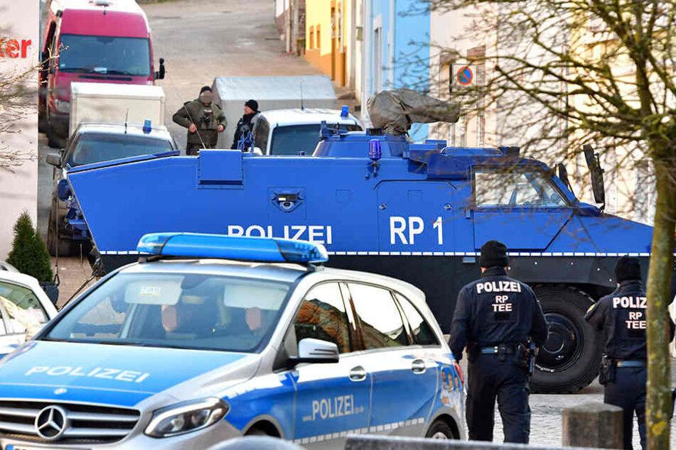 Ein Panzerwagen sichert die Zufahrt in eine Straße, in der in einem Privathaus bei einer Durchsuchung etwa 100 Kilogramm Sprengstoff gefunden wurden.
