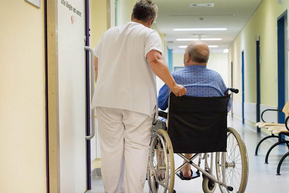 Eine Krankenschwester steht neben einem Patienten im Rollstuhl vor einem Behandlungszimmer.