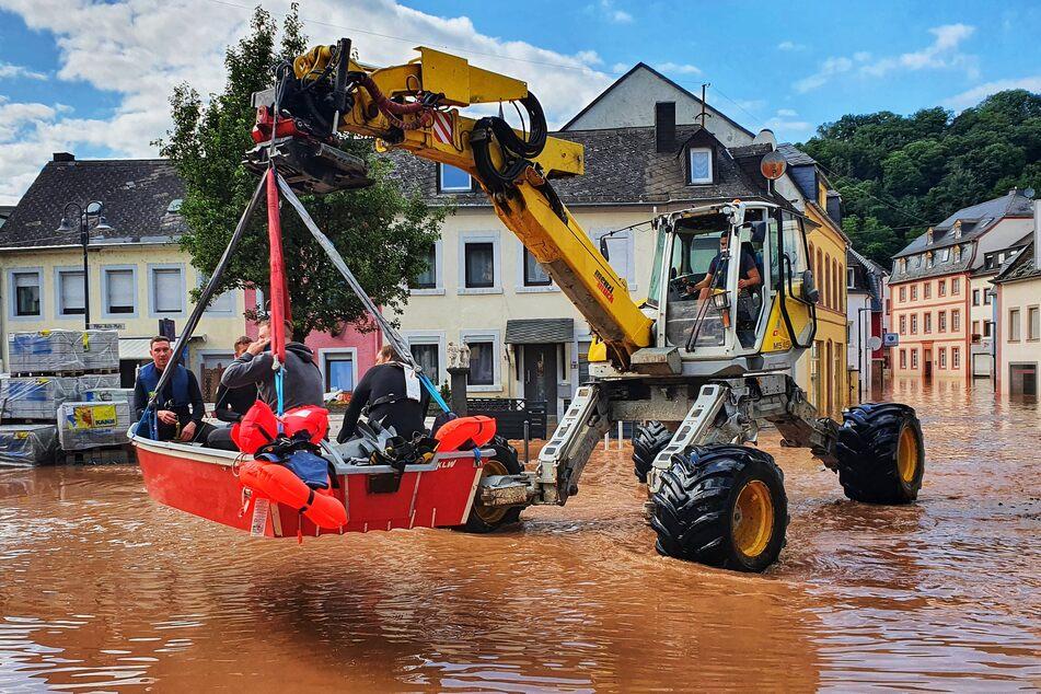 Personen werden mit einem Bagger und einem Boot aus einem überfluteten Teil von Trier gerettet.