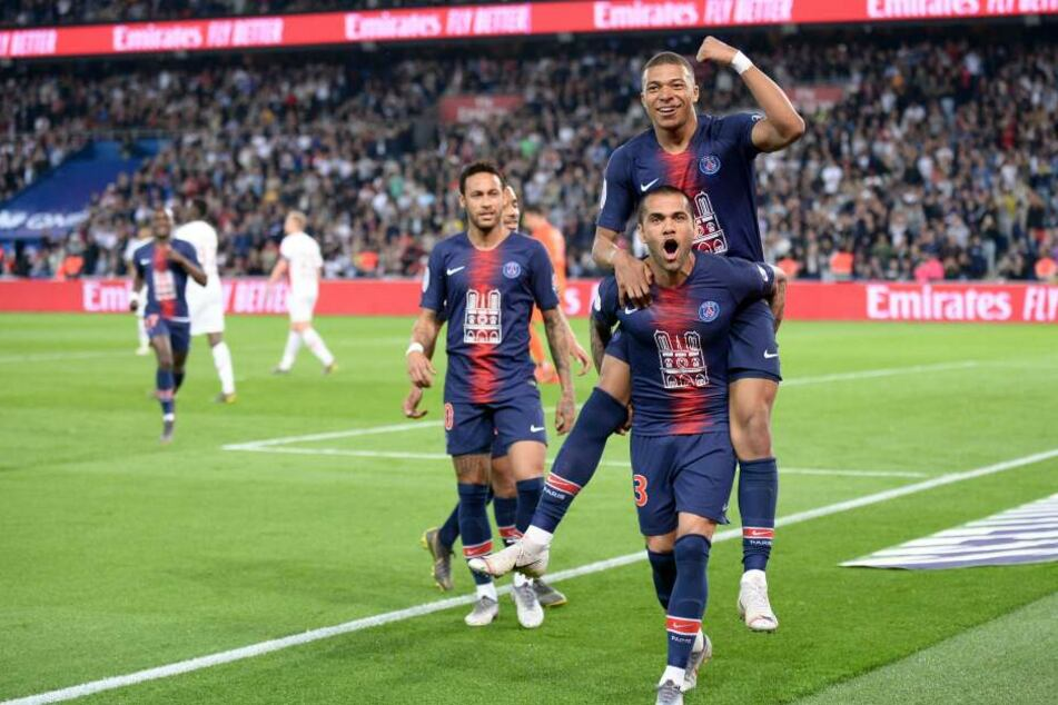 Dani Alves trägt Kylian Mbappé auf Schultern, links daneben schaut Neymar zu.