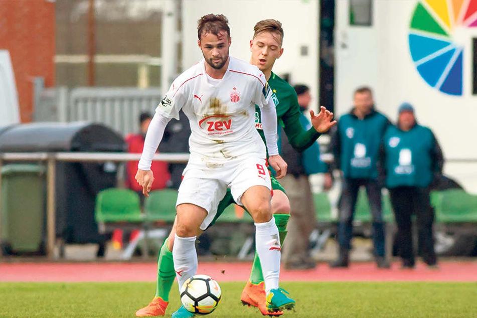 Fabian Eisele sichert den Ball vorm Bremer Jannes Vollert.