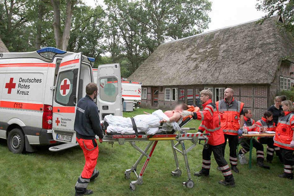 Eine verletzte Person wird auf einer Trage von Sanitätern zum Rettungsfahrzeug gebracht.