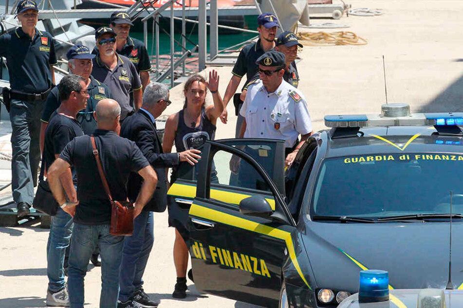 Carola Rackete (Mi.) steigt nach ihrer Ankunft im Hafen von Porto Empedocle in ein Polizeiauto.