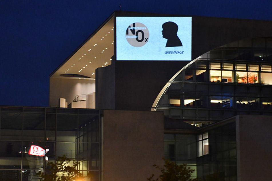 """""""Aktenzeichen ungelöst NOX"""" projizierten Aktivisten auf die Fassade des Bundeskanzleramtes in Berlin."""