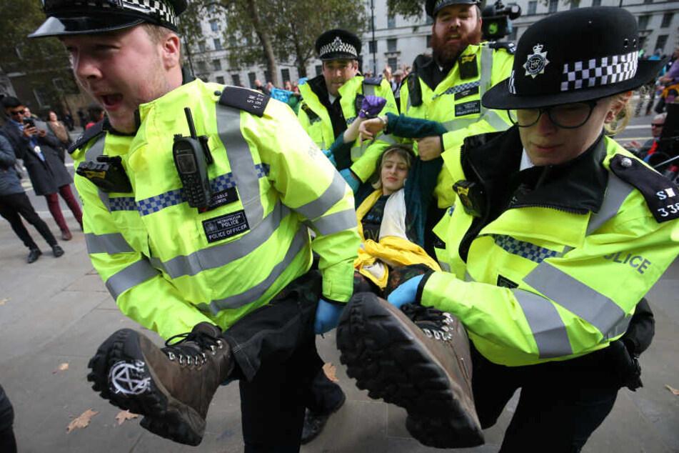 Polizisten tragen eine Extinction Rebellion Demonstrantin von einer Londoner Blockade.