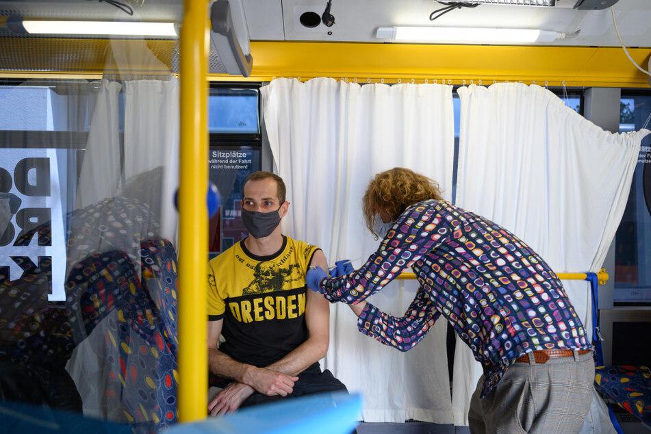 Ein Dynamofan lässt sich vor dem Hygienemuseum in Dresden in einem sogenannten Impfbus gegen das Coronavirus immunisieren.