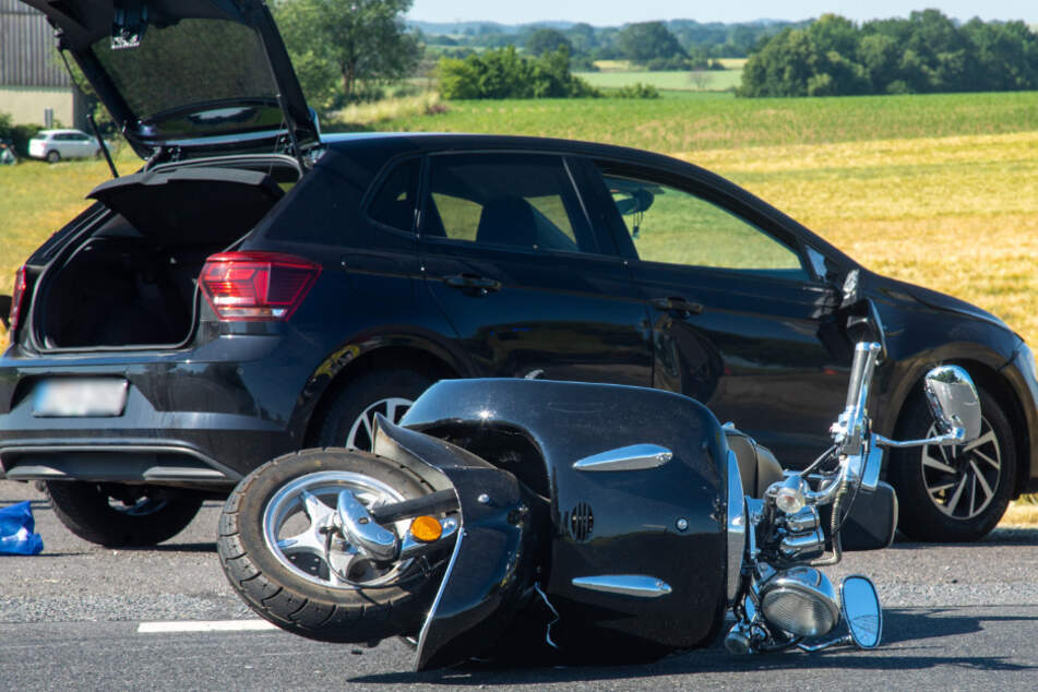 Der Motorroller liegt auf der Seite. Der schwarze VW Polo ist ebenfalls vom Unfall gezeichnet.