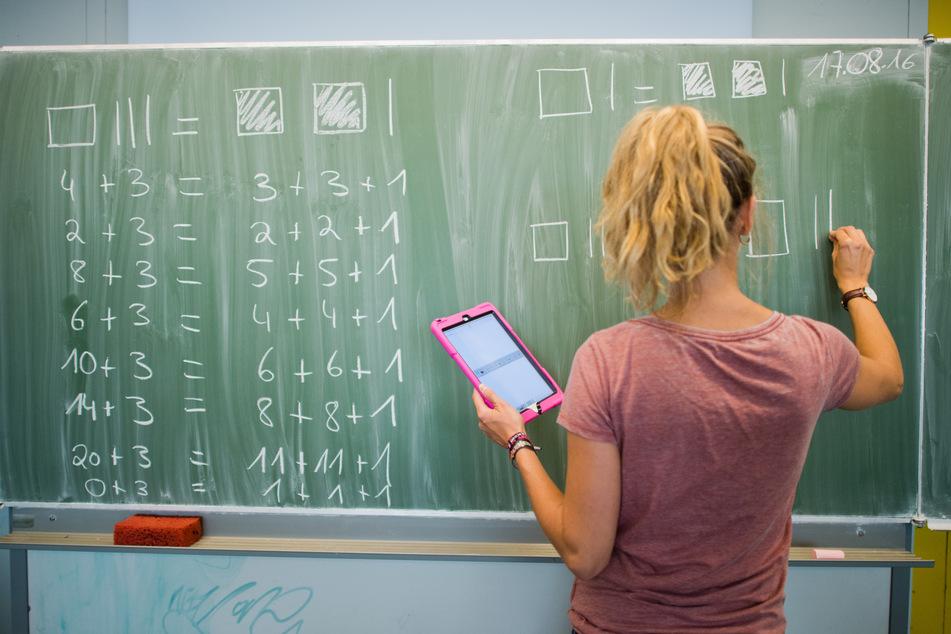Eine junge Lehrerin schreibt an eine Schultafel im Mathematikunterricht und blickt dabei auf einen Tablet-Computer (Archivbild).