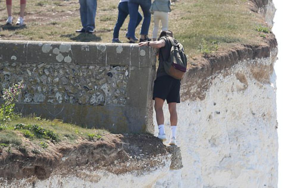 Mann riskiert sein Leben für ein Foto, als er 50 Meter hohe Klippe entlang klettert