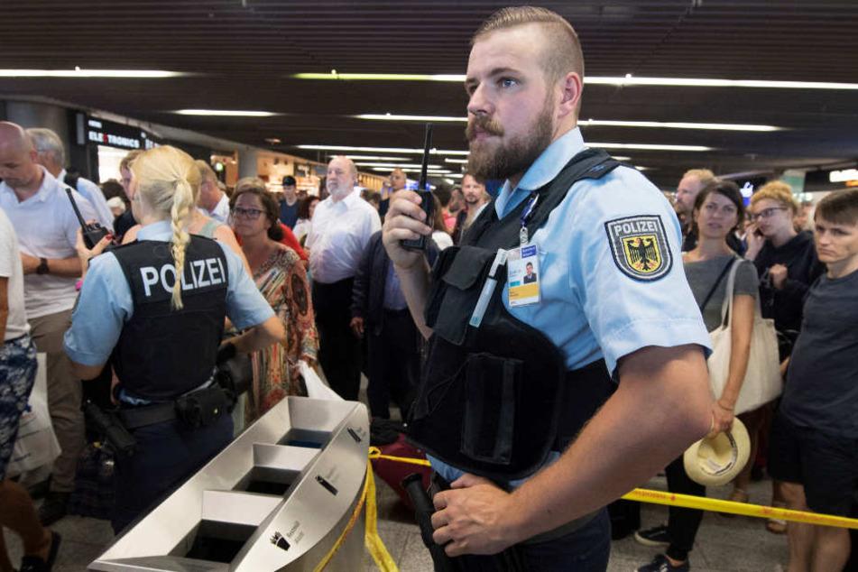 Polizisten und Passagiere stehen in Halle A im Terminal 1 des Flughafens Frankfurt.
