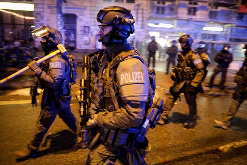 Schwer bewaffnete Spezial-Einsatzkräfte der Polizei laufen durch das Schanzenviertel.