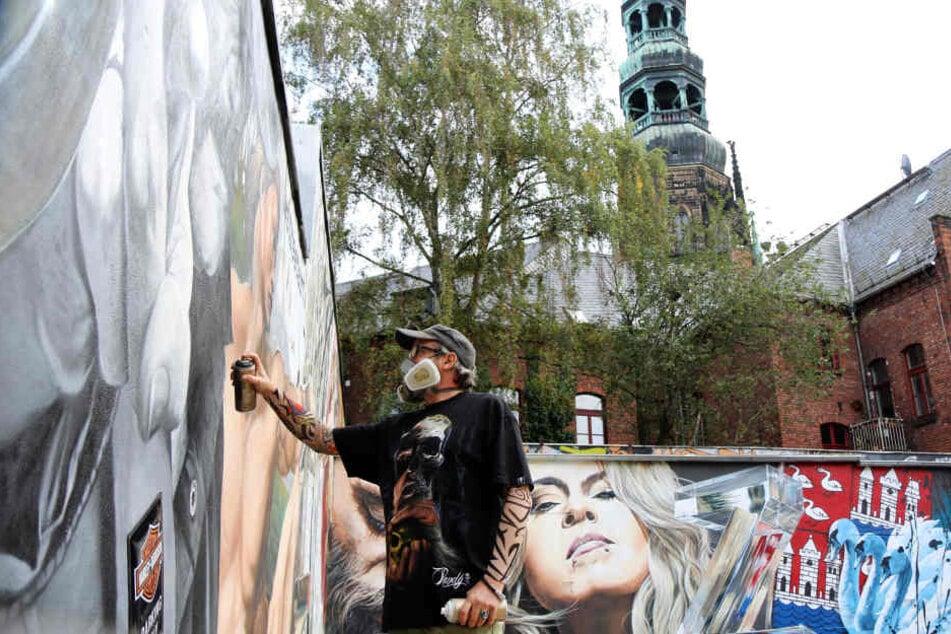 """Streetart-Künstler Jens """"Tasso"""" Müller greift noch einmal zur Spraydose, um das 130 Quadratmeter große Graffiti mit Blick auf den Dom in Zwickau fertigzustellen."""