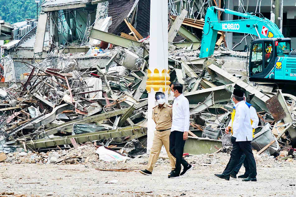Präsident Joko Widodo (M) spricht mit einem Beamten, während er ein erdbebengeschädigtes Regierungsgebäude in Mamuju im Westen der indonesischen Insel Sulawesi inspiziert.