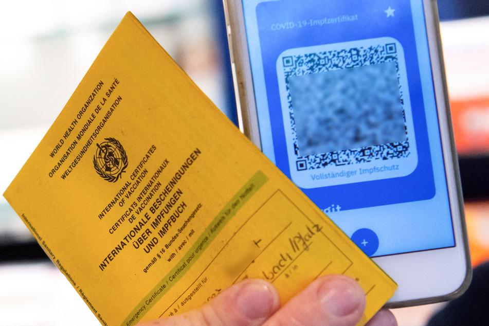 Bayern, München: Ein Apotheker hält einen Impfpass und einen digitalen Impfnachweis in den Händen.