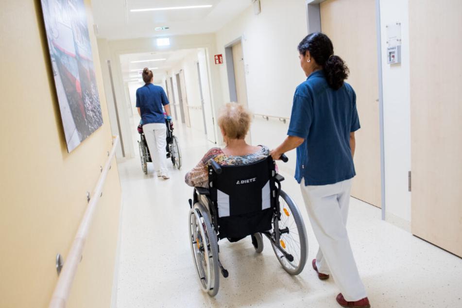 Zwei Pflegerinnen schieben in einem Klinikum Patienten mit Rollstühlen durch einen Flur. (Symbolbild)