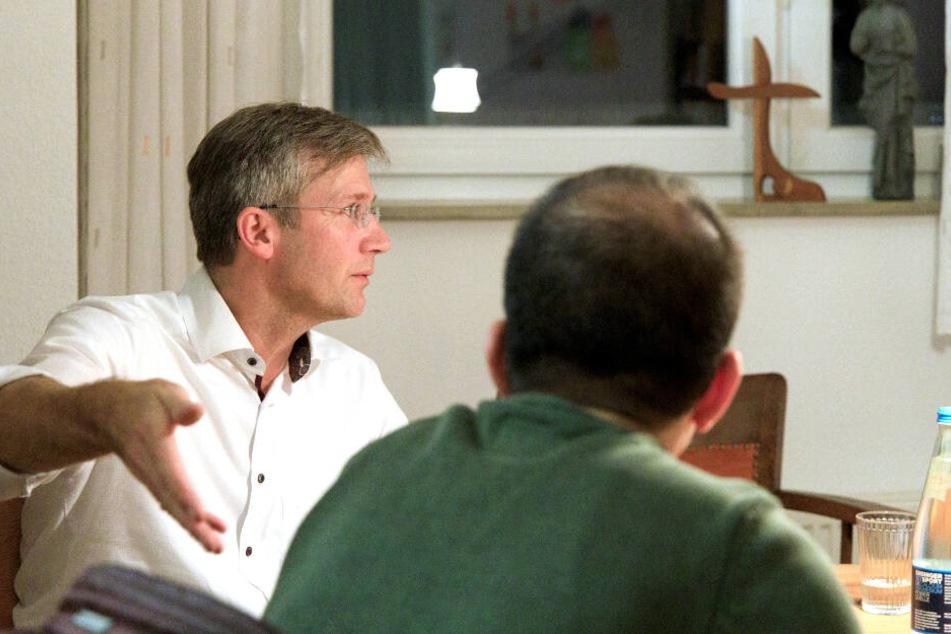 Ein zum christlichen Glauben übergetretener iranischer Flüchtling (rechts) im Gespräch mit einem Pfarrer in Baden-Württemberg.