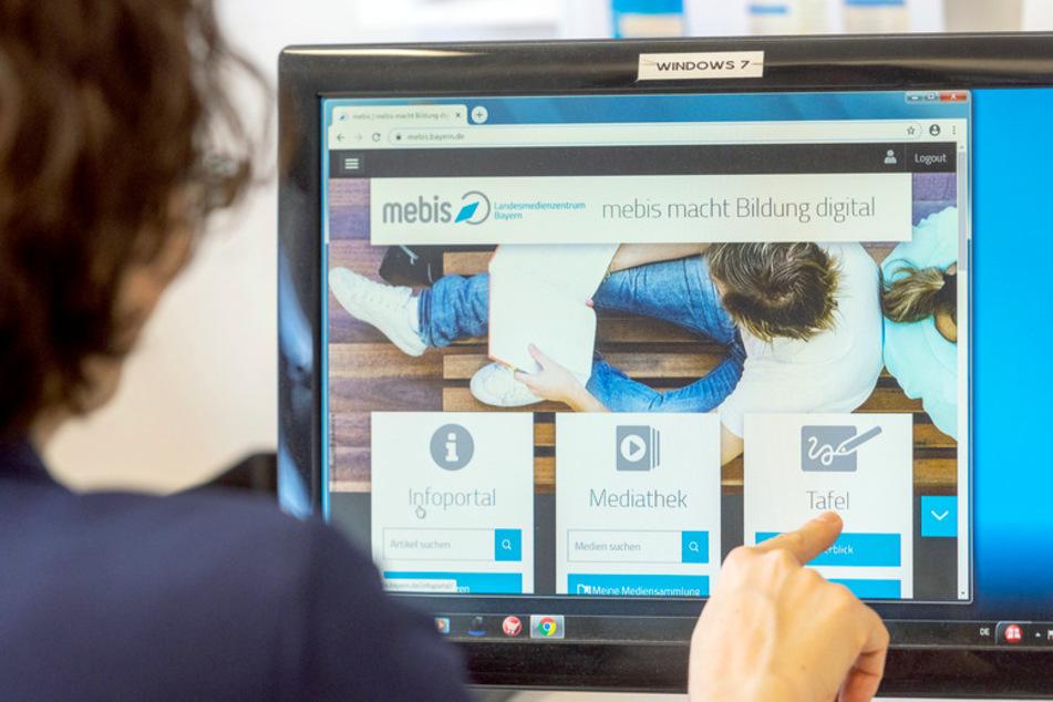 """Eine Lehrerin sitzt vor einem Computermonitor mit dem Programm """"mebis – Landesmedienzentrum Bayern""""."""
