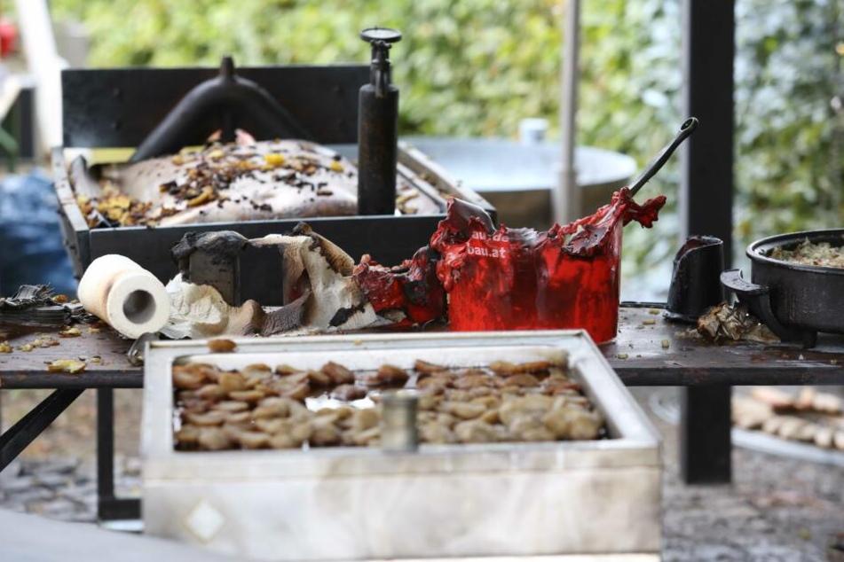 Verbrannte Grill-Utensilien sind auf einem Tisch auf dem Gelände des Festes zu sehen.