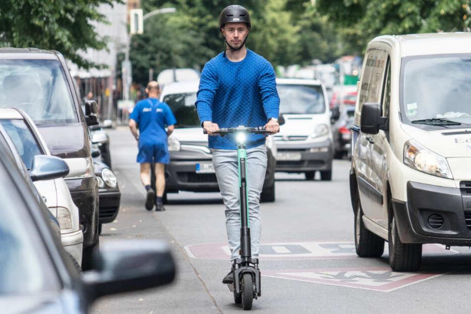Ein Mann fährt mit einem E-Scooter auf der Straße. (Symbolbild)