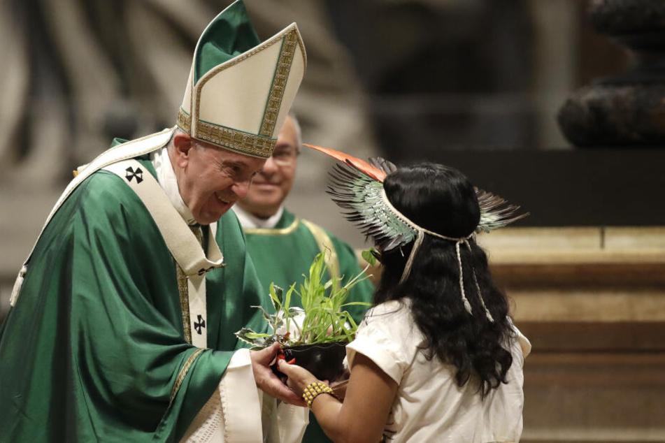 Ein Mädchen aus dem Amazonas-Gebiet überreicht Papst Franziskus während Abschluss-Messe der Bischofssynode über die Amazonas-Region eine Pflanze.