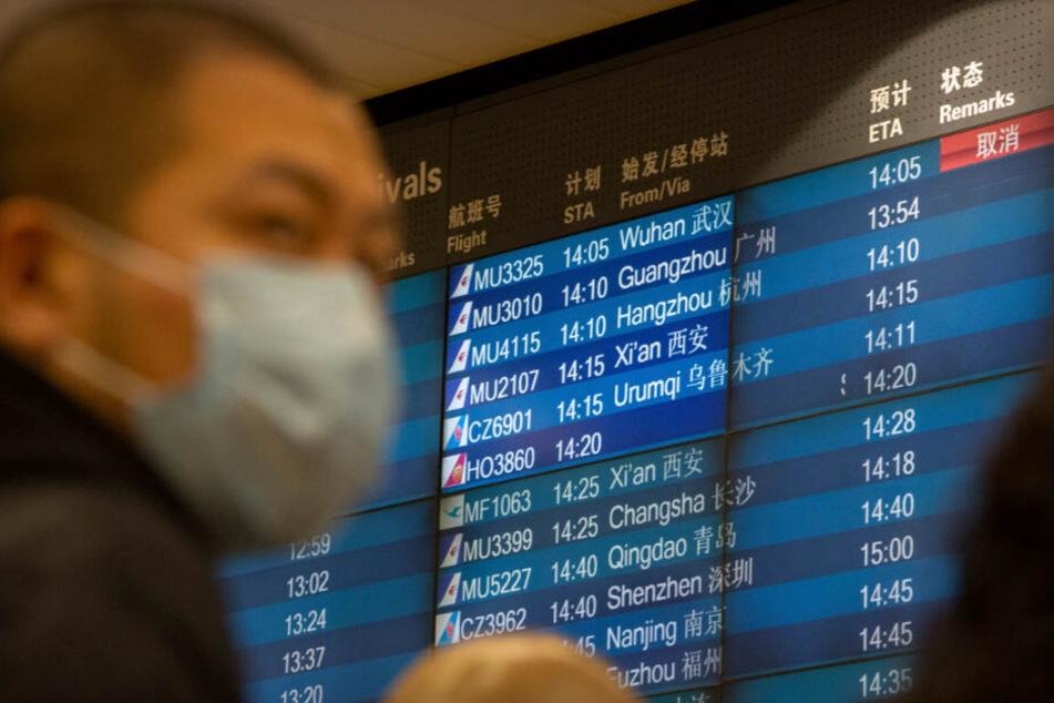 Ein Mann muss am Flughafen erfahren, dass Flüge nach Wuhan gestrichen wurden.