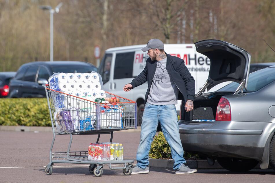 Ein Mann lädt auf einem Parkplatz Toilettenpapier in sein Auto.