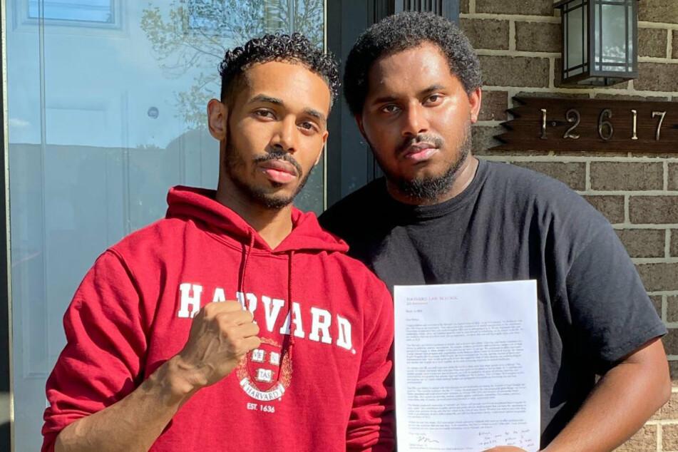 Gemeinsam mit seinem Bruder Reggie (r) posiert Rehan mit der Zugangsbestätigung für Harvard.